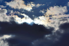 White fluffy clouds in the blue sky.Dramatic cloudscape with sun Stock Photo