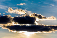 White fluffy clouds in the blue sky. Dramatic cloudscape with su Royalty Free Stock Image