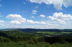 White fluffy clouds in the blue sky over the green mountains. Covered with forests Royalty Free Stock Photos