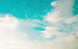 White fluffy clouds in the blue sky. Over a subtle paper texture with scratches Stock Photo