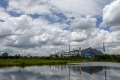 White fluffy clouds in the blue sky and Power plant background.  stock images