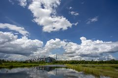 White fluffy clouds in the blue sky and Power plant background.  royalty free stock images