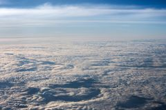 White, fluffy clouds in blue sky. Stratosphere. View from above. White, fluffy clouds in blue sky. Background from clouds. View from the aircraft on the Earth Royalty Free Stock Photography