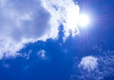 White fluffy clouds in the bright blue sky with light from the S. White fluffy clouds in the bright blue sky with glare and bright light of Sun stock photo