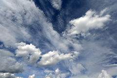 White fluffy clouds on dark blue sky. Partly scattered by wind Stock Image