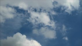 White fluffy clouds and gray rain clouds floating on blue sky in the rainy season stock footage