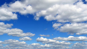 White fluffy clouds over blue sky on sunny day. Time-lapse clip of white fluffy clouds over blue sky on sunny day Royalty Free Stock Photography