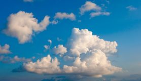 White fluffy cumulus clouds on a blue sky Stock Images
