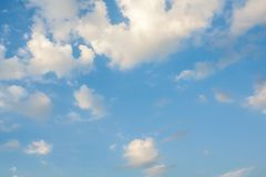 White fluffy cumulus clouds in the blue sky. On a summer day royalty free stock photography