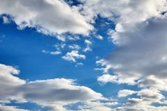 White fluffy soaring clouds on a blue sky. Background stock photography
