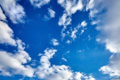 White fluffy clouds on a blue sky background. White fluffy soaring clouds on a blue sky background royalty free stock photo