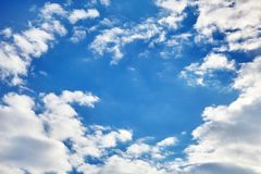 White fluffy clouds on a blue sky background. White fluffy soaring clouds on a blue sky background royalty free stock photos
