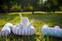A white stuffed toy bunny sitting on the grass. A white fluffy soft stuffed toy rabbit bunny sitting on the grass Royalty Free Stock Photo