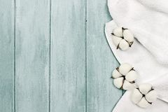 White towel and cotton flowers. White fluffy towel with cotton boll flowers over a blue green background. Image shot from an overhead top view with free space royalty free stock photo