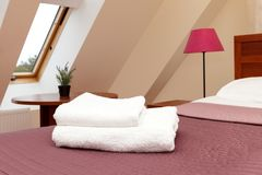 White fluffy towels lie on the bed in the hotel room royalty free stock photo