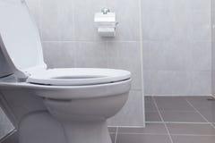 White flush toilet in modern bathroom stock photography
