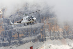 White flying helicopter transporting cargo in Dolomites Royalty Free Stock Images