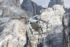 White flying helicopter transporting cargo in the Dolomites, the Royalty Free Stock Image