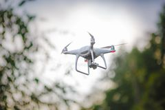 White flying quadrocopter with camera on green forest background stock images