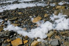 White foam from the big storm waves on the sea pebble coast with large stones. White foam from the big storm waves on the sea pebble coast with large stones Royalty Free Stock Photo