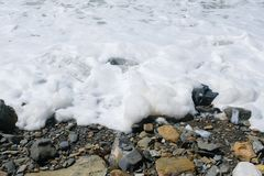 White foam from the big storm waves on the sea pebble coast. White foam from the big storm waves on the sea pebble coast Stock Photos