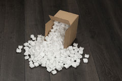White foam pellets from cardboard container. Royalty Free Stock Photos
