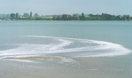 White foam pollution washes into bay when area hit with sudden d Royalty Free Stock Image