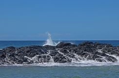 WHITE FOAM AND SEA WATER RUNNING DOWN ROCKS Stock Photography