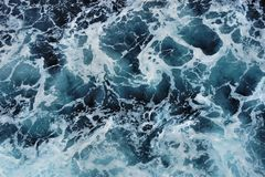 White foam on the surface of the blue sea. Stock Photo