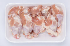 A white foam tray of raw chicken drumsticks from supermarket on. White background, fresh food ingredients concept Stock Photos