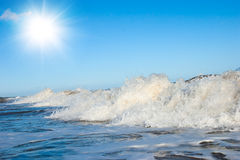 White foam on wave crest. Evening beach. Stock Photos