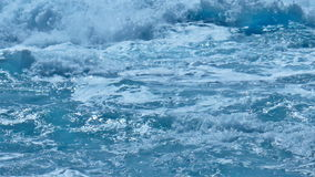 White Foamy Waves Build Up Momentum over Turquoise Sea. Static medium long close up shallow depth of field shot of white foamy waves gaining momentum, and then stock footage