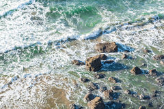 White foamy waves hit small rocks. Clear sea tide washing small rocks near seashore in Oregon Stock Photos