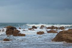 WHITE FOAMY WAVES ROLLING OVER ROCKS IN THE SEA Royalty Free Stock Image