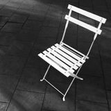 White foldable chair on dark background royalty free stock photo