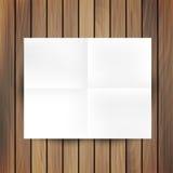 White folded paper mockup card isolated on wood background Royalty Free Stock Image
