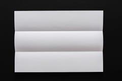 White folded sheet of paper on black background Royalty Free Stock Image