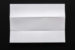 White folded sheet of paper on black background Stock Photos