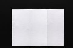 White folded sheet of paper on black background Stock Photo