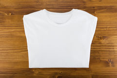 White folded t-shirt template on a wooden background. stock photo