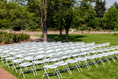 White Folding Chairs on Green Lawn Stock Images