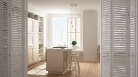 White folding door opening on modern white kitchen with wooden details in contemporary luxury apartment, interior design,. Architect designer concept, blur royalty free stock photo