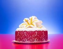 White fondant cake decorated with red lace and edible candy lily. On red-blue background stock images