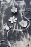 White fondant flowers and butterfly. On wooden black board with silver ribbon Royalty Free Stock Images