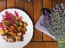 White food plate with meat and potatoes. White food plate with meat, cabbage and potatoes, lavender, black sunglasses and purple wallet, on a wooden brown table Stock Image