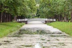 White Footbridge in Green Park. White footbridge across narrow river in landscape park Royalty Free Stock Image