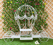 White forged a coach in the blooming garden. Wedding decoration stock photo