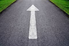 White forward arrow sign on grey asphalt road . White forward arrow sign on grey asphalt road through the green grass field Stock Image