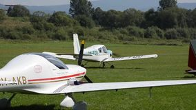 White four seat propeller-driven Zlin Z43 airplane moves on grass landing strip in small airport stock video footage