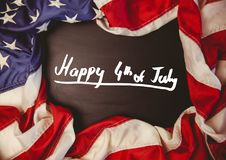 White fourth of July graphic against chalkboard and american flag. Digital composite of White fourth of July graphic against chalkboard and american flag Stock Photography